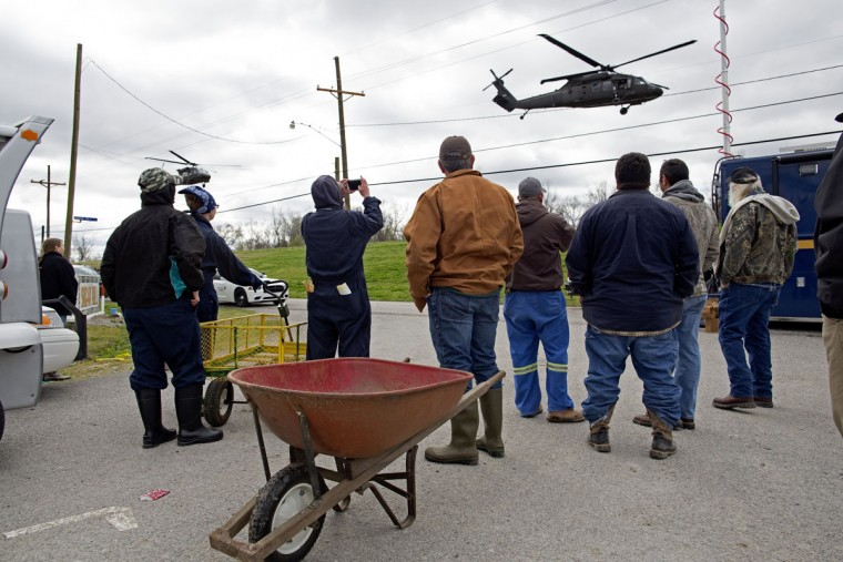 Residents of the Sugar Hill RV Park watch a pair of helicopters from the Louisiana National Guard carrying Louisiana Gov. John Bel Edwards and Assistant Adjutant General of the Louisiana National Guard Major General Stephen Dabadie depart in Convent, La., Wednesday, Feb. 24, 2016. Edwards and Dabadie met with emergency crews to organize the aftermath of a tornado touch down that caused serious damage the day before. (AP Photo/Max Becherer)