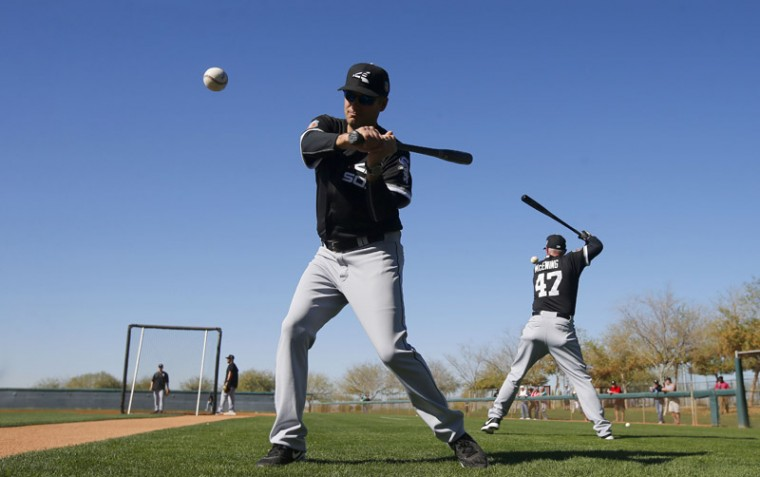 Chicago White Sox manager Robin Ventura, left, and third base coach Joe McEwing (47) hit infield grounders to players during a spring training baseball workout Monday in Glendale, Ariz. (Ross D. Franklin/AP)