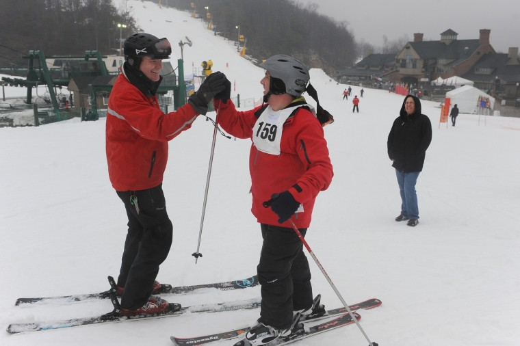 Coach Tim Collard, left, high-fives skier Paul Howard Jr. of Baltimore, who skis with the Carroll county team, after he crossed the finish line in a slalom event at the winter 2016 Maryland Special Olympics, which was held at Whitetail Ski Resort.  (Barbara Haddock Taylor/Baltimore Sun)