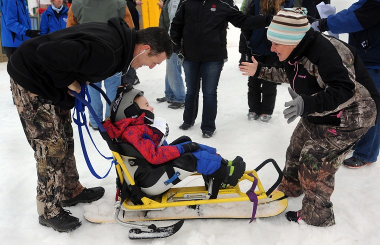 Ryan Drimal, 8 of Berlin MD, gets some encouragement from his parents, Rob, left, and Stephanie, right, at the winter 2016 Special Olympics, which was held at Whitetail Ski Resort. Ryan participated in the Super Glide ski event.  (Barbara Haddock Taylor/Baltimore Sun)