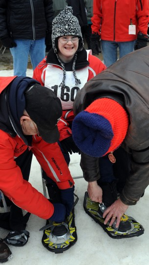 Nicole Hurley of Carroll County smiles as she gets some help putting on her snowshoes at the winter 2016 Maryland Special Olympics, which was held at Whitetail Ski Resort.  (Barbara Haddock Taylor/Baltimore Sun)