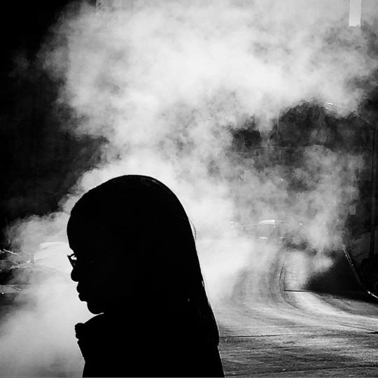 A pedestrian is silhouetted by steam on St. Paul Place in Baltimore.   (Lloyd Fox/Baltimore Sun)