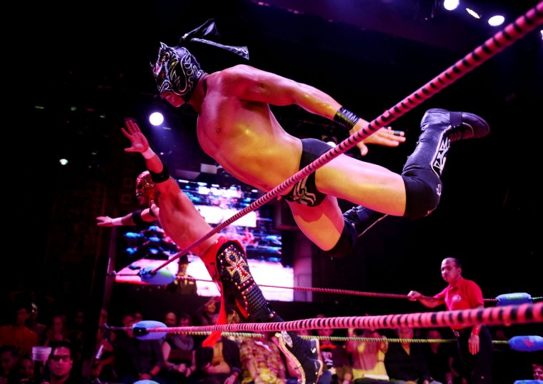 "Wrestlers Dragon Lee and Rey Horus leap towards their opponents during the Lucha Va Voom's ""Crazy in Love"" show at the Mayan Theatre in downtown Los Angeles, California on February 10, 2016. (MARK RALSTON/AFP/Getty Images)"