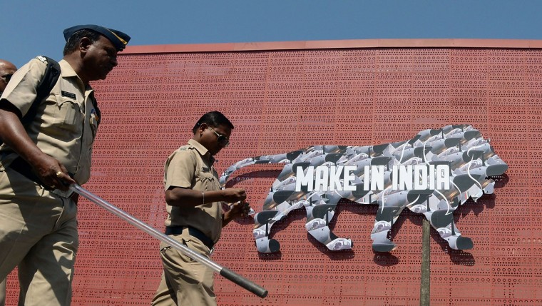 Indian policemen walk past a logo at the venue for the 'Make in India' showcase week in Mumbai on February 11, 2016. (INDRANIL MUKHERJEE/AFP/Getty Images)