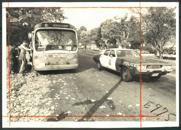 A city policeman keeps an eye on a bus at Roland Park Junior High School on Oct. 16, 1975. (Baltimore Sun photo by Carl D. Harris)