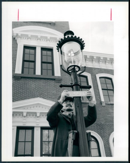 March 11, 1992: Barrie Cowden is dressed in a period costume of a lamplighter in the late 1800 s as he places a plaque on one of the original Welsbach three mantled Victorial Boulevard style lamps with original eight foot Baltimore fluted poles. Lamps like this were common in Baltimore from 1867 to 1957. Photo by Barbara Haddock for The Baltimore Sun.