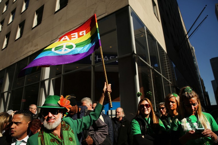 A man holds up a Gay Pride flag at the annual St. Patrick's Day parade, one of the largest and oldest in the world, on Thursday in New York City. Now that a ban on openly gay groups has been dropped, New York Mayor Bill de Blasio is attending the parade for the first time since he became mayor in 2014. The parade goes up Fifth Avenue ending at East 79th Street and will draw an estimated 2 million spectators along its 35-block stretch.  (Spencer Platt/Getty Images)