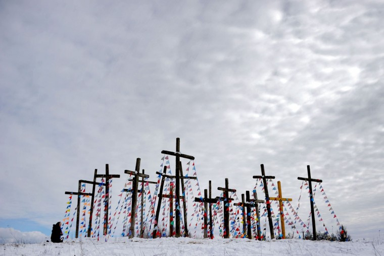 A woman prays on a hill with wooden crosses as she celebrates Palm Sunday in the town of Oshmiany, some 130 kilometres northwest of Minsk, on March 20, 2016. (AFP PHOTO / SERGEI GAPON)