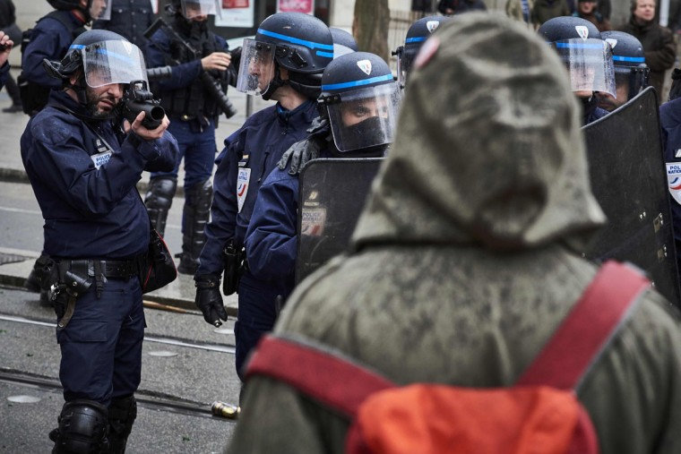 A police officer aims a flash-ball at protesters during a demonstration on March 9, 2016, in Lyon, central-eastern France, as part of a nationwide day of protest against proposed labour reforms. France faced a wave of protests on March 9 against deeply unpopular labour reforms that have divided an already-fractured Socialist government and raised hackles in a country accustomed to iron-clad job security. (AFP / Jean-Philippe Ksiazek)