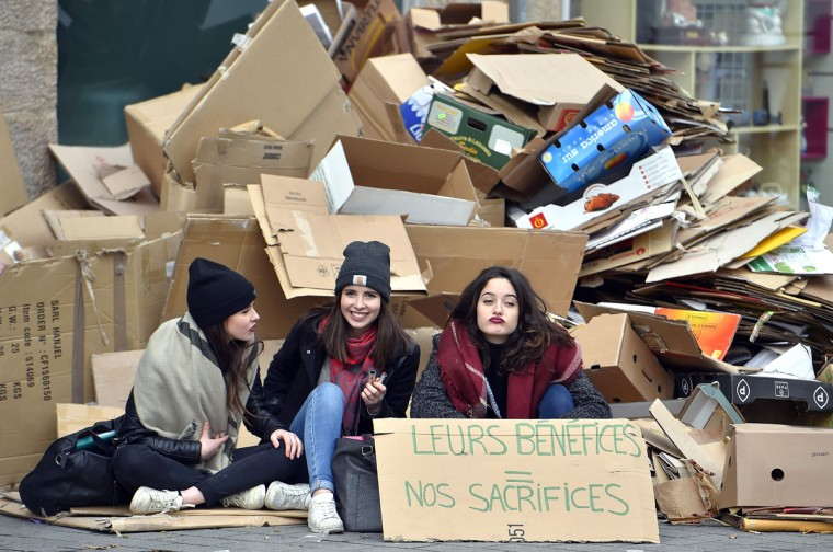"Girls sit next to cardboard boxes and a placard reading ""their profits, our sacrifices"", during the nationwide day of protest against proposed labour reforms, on March 9, 2016 in Nantes, western France. France faced a wave of protests against deeply unpopular labour reforms that have divided an already-fractured Socialist government and raised hackles in a country accustomed to iron-clad job security. (AFP / Loic Venance)"