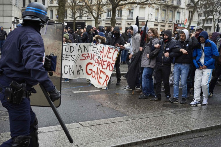Police face protesters during a demonstration on March 9, 2016, in Lyon, central-eastern France, as part of a nationwide day of protest against proposed labour reforms. France faced a wave of protests on March 9 against deeply unpopular labour reforms that have divided an already-fractured Socialist government and raised hackles in a country accustomed to iron-clad job security. (AFP / Jean-Philippe Ksiazek)