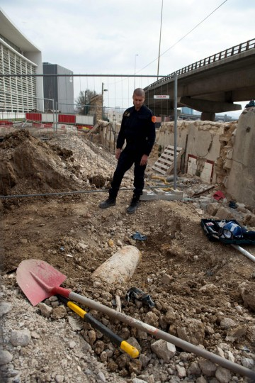 Bomb-clearing expert Christophe Perrier looks at a WWII bomb before neutralising it in the Arenc area in Marseille, southern France, on March 13, 2016. Careful precautions were taken on March 13 in Marseille to try to defuse and blow up at sea a World War II bomb from 1944 discovered on a construction site. (Bertrand Langlois/ AFP/Getty Images)