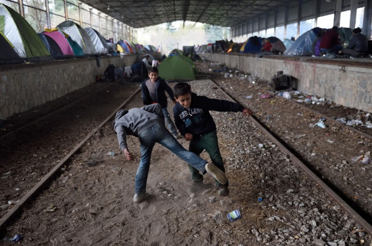 Young boys play with a can near tents lined up at a makeshift camp at the Greek-Macedonian border, near the Greek village of Idomeni, on March 16, 2016, where thousands of refugees and migrants are stranded by the Balkan border blockade. Some 1,500 migrants who managed to cross into Macedonia, despite the border being closed to them for a week, have been sent back to Greece by Macedonian troops, officials said on March 15. (Daniel Mihailescu/AFP/Getty Images)