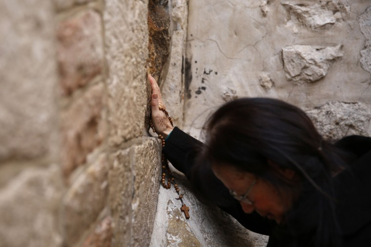 A Catholic pilgrim prays at the 5th station of the Via Dolorosa (Way of Suffering) in Jerusalems Old City during the Good Friday procession on March 25, 2016. Many Christian pilgrims took part in processions along the route where according to tradition Jesus Christ carried the cross during his last days. (Gali Tibbon/AFP/Getty Images)
