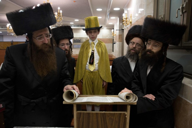 Ultra-Orthodox Jews and a dressed up boy read the book of Esther at a synagogue in the Israeli city of Beit Shemesh on March 23, 2016 during the feast of Purim. The carnival-like Purim holiday is celebrated with parades and costume parties to commemorate the deliverance of the Jewish people from a plot to exterminate them in the ancient Persian empire 2,500 years ago, as recorded in the Biblical Book of Esther. (AFP Photo/Menahem Kahana)