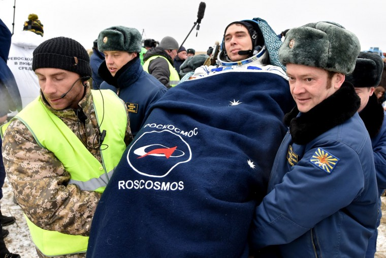 Ground personnel carry International Space Station (ISS) crew member Sergei Volkov of Russia after landing near the town of Dzhezkazgan, Kazakhstan, on March 2, 2016. (KIRILL KUDRYAVTSEV/AFP/Getty Images)