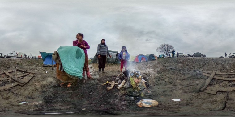 A family stand besides their fire at the Idomeni refugee camp on the Greek Macedonia border on March 16, 2016 in Idomeni, Greece. The decision by Macedonia to close its border to migrants last week has left thousands of people stranded at the Greek transit camp. The closure, following the lead taken by neighbouring countries, has effectively sealed the so-called western Balkan route, the main migration route that has been used by hundreds of thousands of migrants to reach countries in western Europe such as Germany. Humanitarian workers have described the conditions at the camp as desperate, which has been made much worse by recent spells of heavy rain. (Photo by Matt Cardy/Getty Images)