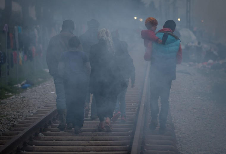 A family walks through camp fire smoke at the Idomeni refugee camp on the Greek Macedonia border on March 16, 2016 in Idomeni, Greece. The decision by Macedonia to close its border to migrants last week has left thousands of people stranded at the Greek transit camp. The closure, following the lead taken by neighbouring countries, has effectively sealed the so-called western Balkan route, the main migration route that has been used by hundreds of thousands of migrants to reach countries in western Europe such as Germany. Humanitarian workers have described the conditions at the camp as desperate, which has been made much worse by recent spells of heavy rain. (Photo by Matt Cardy/Getty Images)
