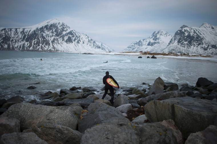 A man goes to surf at the snowy beach of Flackstad, near Ramberg, in Lofoten archipelago, Arctic Circle, on March 12, 2016. Surfers from all over the world come to Lofoten islands to surf in extreme conditions. Ocean temperature is 5-6 °C, air temperature around 0°C in spite of a weather very unstable. (OLIVIER MORIN/AFP/Getty Images)