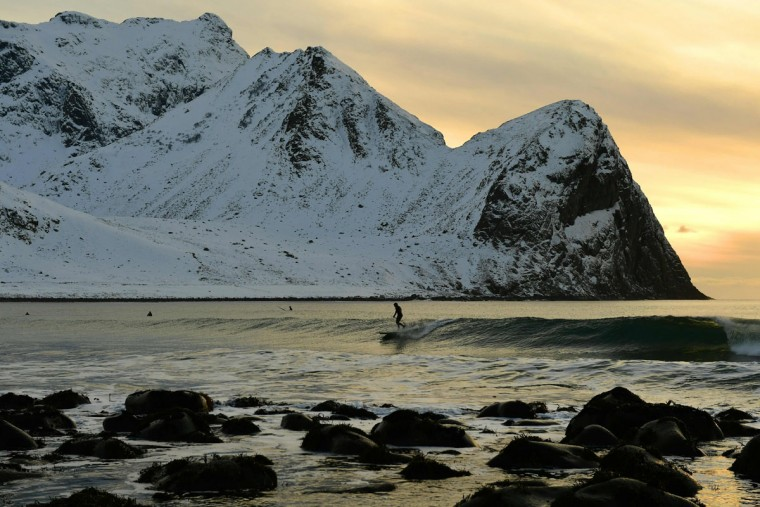 A surfer rides a wave at the end of afternoon at the snowy beach of Unstad, in Lofoten archipelago, Arctic Circle, on March 9, 2016. (OLIVIER MORIN/AFP/Getty Images)