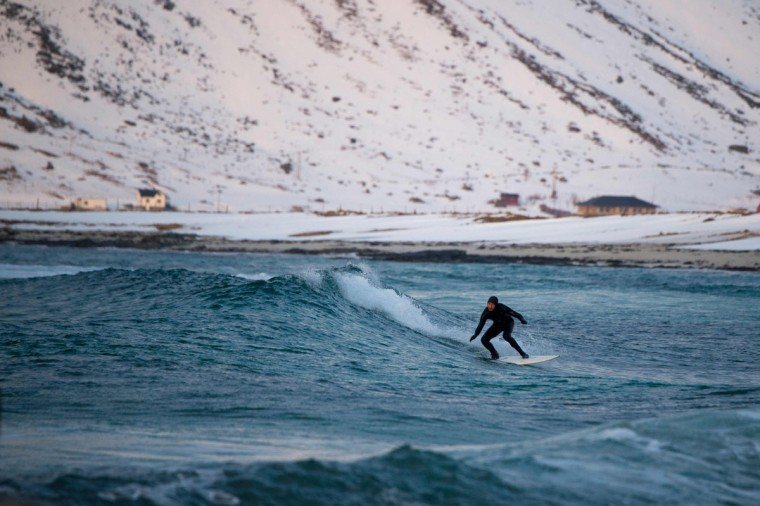 A surfer rides a wave at the snowy beach of Flackstad, in Lofoten Island, Arctic Circle, on March 12, 2016. (OLIVIER MORIN/AFP/Getty Images)