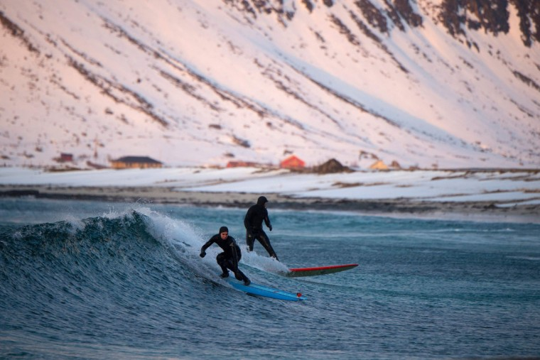 Surfers ride a wave at night time at the snowy beach of Flackstad, in Lofoten Island, Arctic Circle, on March 12, 2016. (OLIVIER MORIN/AFP/Getty Images)