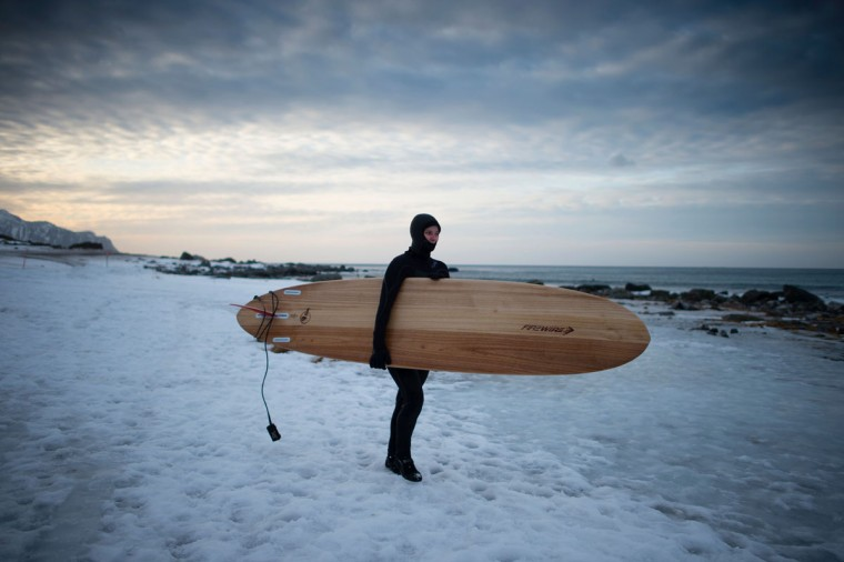 A girl goes to surf at the snowy beach of Flackstad, near Ramberg, in Lofoten archipelago, Arctic Circle, on March 12, 2016. Surfers from all over the world come to Lofoten islands to surf in extreme conditions. Ocean temperature is 5-6 °C, air temperature around 0°C in spite of a weather very unstable. (OLIVIER MORIN/AFP/Getty Images)