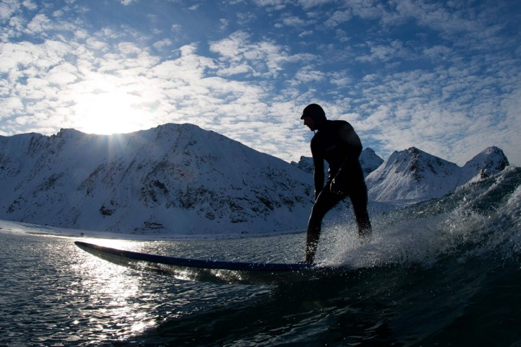 A surfer rides a wave at the snowy beach of Unstad, in Lofoten Island, Arctic Circle, on March 9, 2016. (OLIVIER MORIN/AFP/Getty Images)