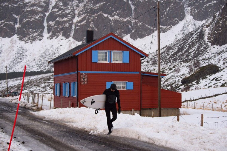 A surfer leaves the snowy beach of Unstad after surfing, in Lofoten Island, Arctic Circle, on March 10, 2016. (OLIVIER MORIN/AFP/Getty Images)