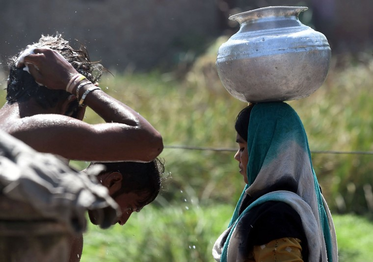 A Pakistani woman carries a water pot through a makeshift settlement as men bathe using a communal water pump in Lahore on March 22, 2016. International World Water Day is held annually on March 22 to focus global attention on the importance of water and advocate for sustainable water resource management. (Arif Ali/AFP/Getty Images)