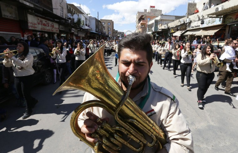 Syrian Christian Roman Catholic scouts parade after a mass marking Palm Sunday in the capital Damascus, on March 20, 2016. The ceremony is a landmark in the Christian calendar, marking the triumphant return of Christ to Jerusalem the week before his death, when a cheering crowd greeted him waving palm leaves. Palm Sunday marks the start of the most solemn week in the Christian calendar. (AFP PHOTO / LOUAI BESHARA)
