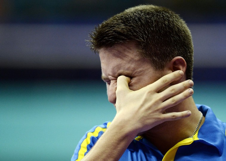 Kristian Karlsson of Sweden pokes his eye after being hit by a shot from Ruwen Filus of Germany during their men's singles round match of the 2016 World Team Table Tennis Championships at the Malawati Stadium in Shah Alam on Wednesday. (MANAN VATSYAYANA/AFP/Getty Images)