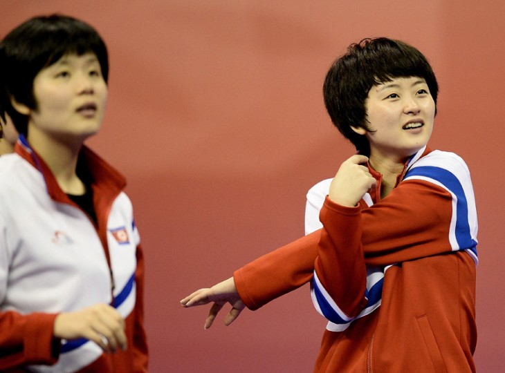 Ri Myong-Sun of North Korea (R) stretches after defeating Romania during their women's singles quarter-final classification match at the 2016 World Team Table Tennis Championships at Malawati Stadium in Shah Alam on March 3, 2016. (MANAN VATSYAYANA/AFP/Getty Images)