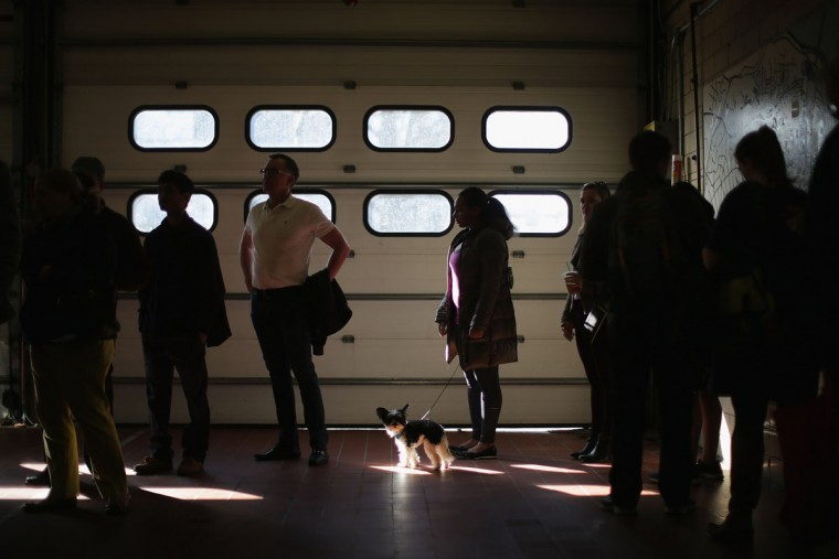 Leo the dog and his owner Nina Ward wait in line with other voters to cast their ballots inside the Arlington County Fire Station 10 during Super Tuesday voting March 1, 2016 in Arlington, Virginia. Officials are expecting a record turnout of voters in Virginia, one of a dozen states holding presidential primaries or caucuses. (Photo by Chip Somodevilla/Getty Images)