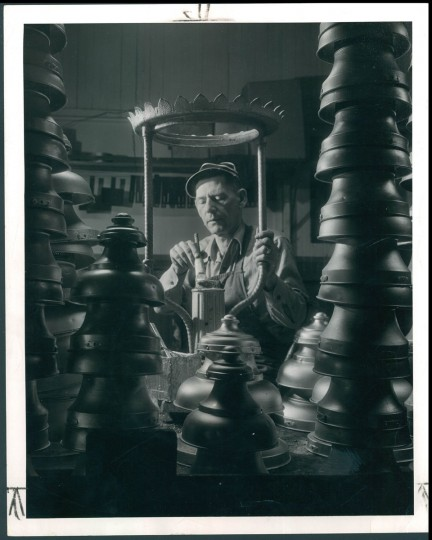 Thomas Cotter, machinist, paints a gas street lamp's frame in this photo from June 15, 1952. Photo by A. Aubrey Bodine for The Baltimore Sun.