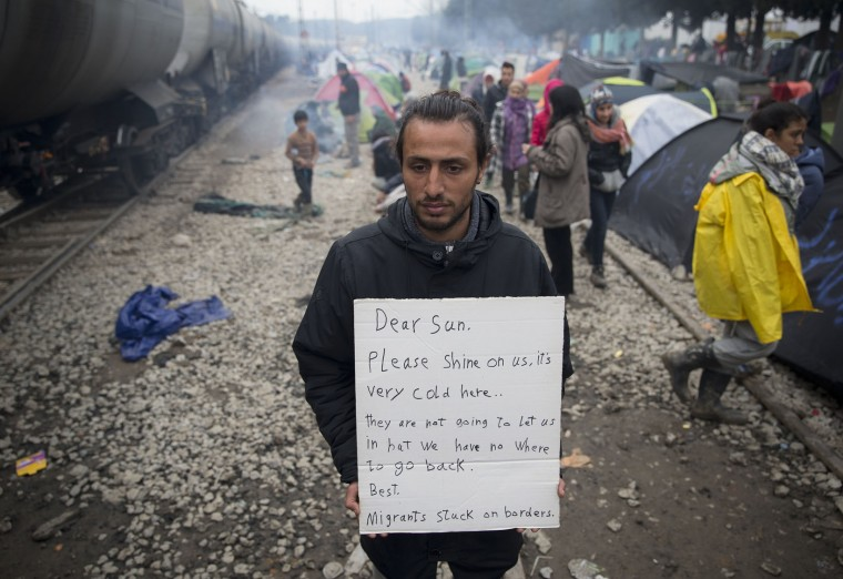 A man holds a banner near tents set up near railway tracks at the northern Greek border point of Idomeni, Greece, Wednesday, March 16, 2016. Leaders of the EU's 28 divided nations plan to reconvene in Brussels this week in hopes of ironing out disagreements on a proposed agreement with Turkey in the migrants crisis. (AP Photo/Vadim Ghirda)