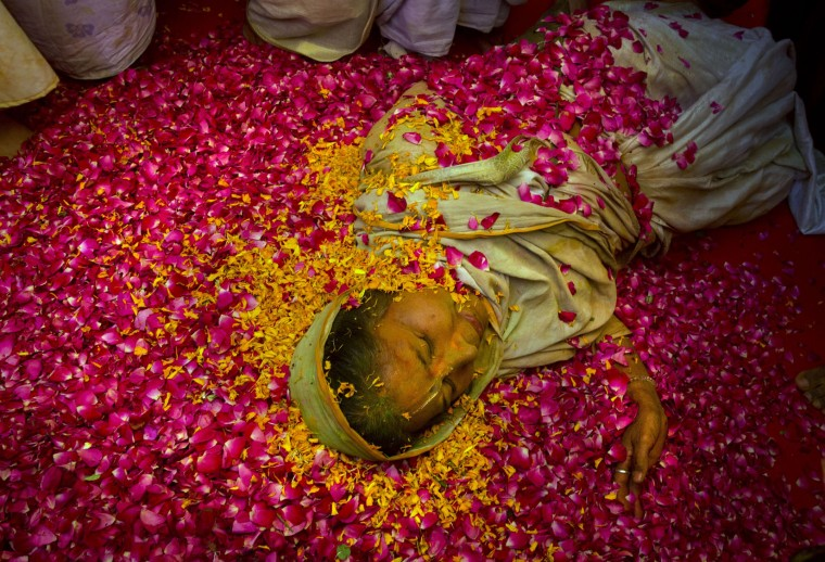 An Indian Hindu widow lies on a bed of flower petals during Holi celebrations at the Gopinath temple, 180 kilometres (112 miles) south-east of New Delhi, India Monday, March 21, 2016. A few years ago this joyful celebration was forbidden for Hindu widows. Like hundreds of thousands of observant Hindu women they would have been expected to live out their days in quiet worship, dressed only in white, their very presence being considered inauspicious for all religious festivities. (AP Photo/Manish Swarup)