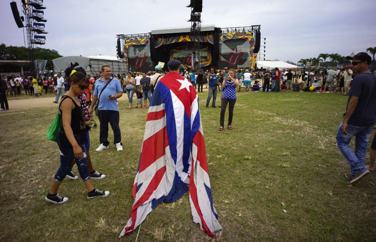 A fan walks carrying the Cuban and the UK flags draped on his back, at the venue where the Rolling Stones will play their concert in Havana, Cuba, Friday, March 25, 2016. The Stones are performing in a free concert in Havana, becoming the most famous act to play Cuba since its 1959 revolution.(Ramon Espinosa/ AP Photo)