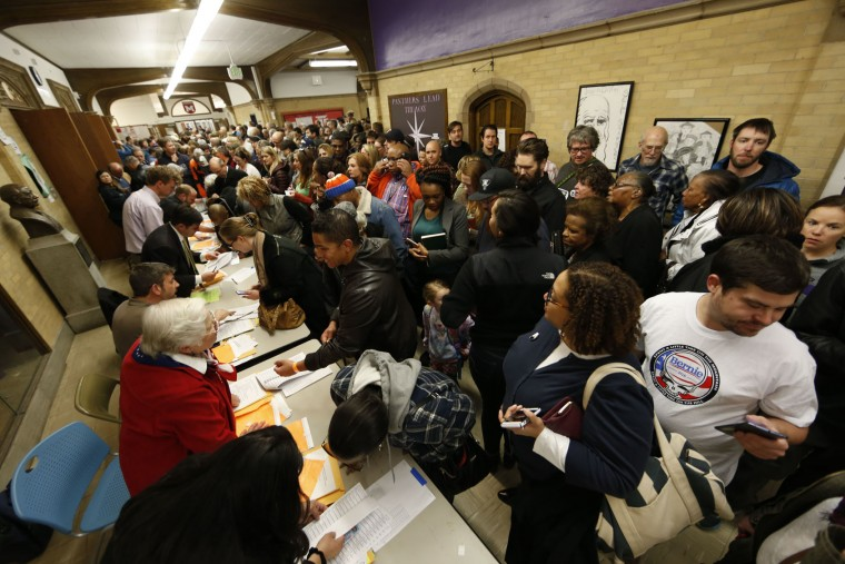 Voters crowd into foyer of Smiley Middle School to check in with their precinct captains to attend a Democratic caucus late Tuesday, March 1, 2016, in Denver. Colorado is one of 12 states casting votes for party nominees on Super Tuesday, which offers candidates the chance to garner the biggest single-day delegate haul of the nomination contests. (AP Photo/David Zalubowski)