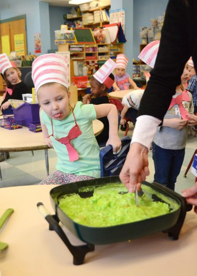 Kindergartener Payton Kolis reacts as her teacher Mara Wooley makes green eggs and ham at C.T. Plunkett School in Adams, Mass., as part of Dr. Seuss's birthday celebration for Read Across America on Wednesday, March 2, 2016. (Gillian Jones/The Berkshire Eagle via AP)