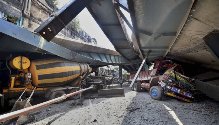 Vehicles are seen trapped under a partially collapsed overpass in Kolkata, India, on Thursday. Rescuers dug through large chunks of debris from the overpass that collapsed while under construction, killing many people and injuring scores of others, officials said. (Swapan Mahapatra/Press Trust of India via AP)