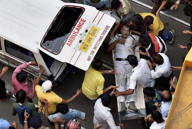 An injured traffic police officer is rushed to an ambulance after an under construction overpass partially collapsed in Kolkata, India. (Swapan Mahapatra/Press Trust of India via AP)
