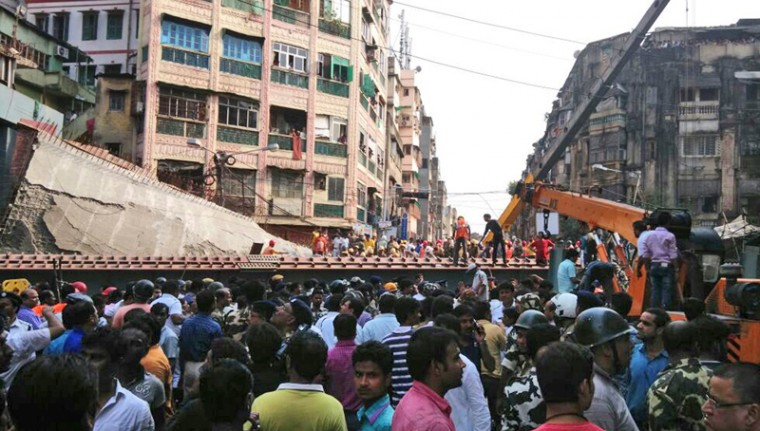People watch as locals and rescue workers clear the rubble of a partially collapsed overpass in Kolkata. Dozens have been injured and several were killed when a portion of the under-construction overpass collapsed in a congested area in the eastern Indian city. (Bikas Das/AP)