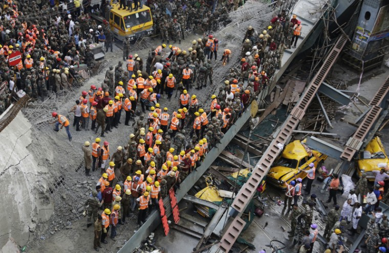 Indian soldiers and rescue workers work on a partially collapsed overpass in Kolkata, India, on Thursday. A long section of a road overpass under construction collapsed Wednesday in a crowded Kolkata neighborhood, with tons of concrete and steel slamming into midday traffic, killing several and injuring many. (Bikas Das/AP)