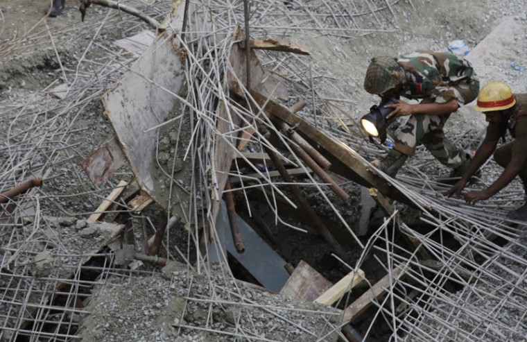 An Indian soldier looks for survivors underneath the debris of a partially collapsed overpass in Kolkata, India, on Thursday. (Bikas Das/AP)
