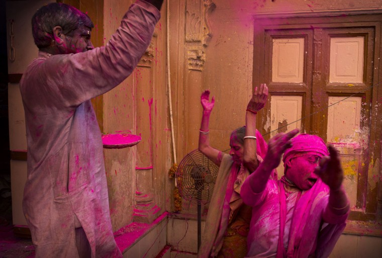 Locals and Indian Hindu widows throw flower petals and colored powder during Holi celebrations at the Gopinath temple, 180 kilometres (112 miles) south-east of New Delhi, India, Monday, March 21, 2016. A few years ago this joyful celebration was forbidden for Hindu widows. Like hundreds of thousands of observant Hindu women they would have been expected to live out their days in quiet worship, dressed only in white, their very presence being considered inauspicious for all religious festivities. (AP Photo/Manish Swarup)