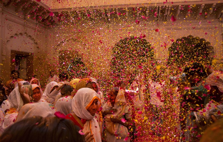 Indian Hindu widows throw flower petals and colored powder during Holi celebrations at the Gopinath temple, 180 kilometres (112 miles) south-east of New Delhi, India Monday, March 21, 2016. A few years ago this joyful celebration was forbidden for Hindu widows. Like hundreds of thousands of observant Hindu women they would have been expected to live out their days in quiet worship, dressed only in white, their very presence being considered inauspicious for all religious festivities. (AP Photo/Manish Swarup)