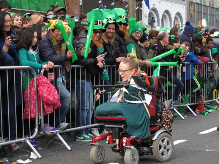 Joanne O'Riordan, 19, Ireland's most high-profile campaigner for disabled rights and this year's grand marshal of the St. Patrick's Day parade, greets spectators on O'Connell Street, Dublin, on Thursday. (Shawn Pogatchnik/AP)