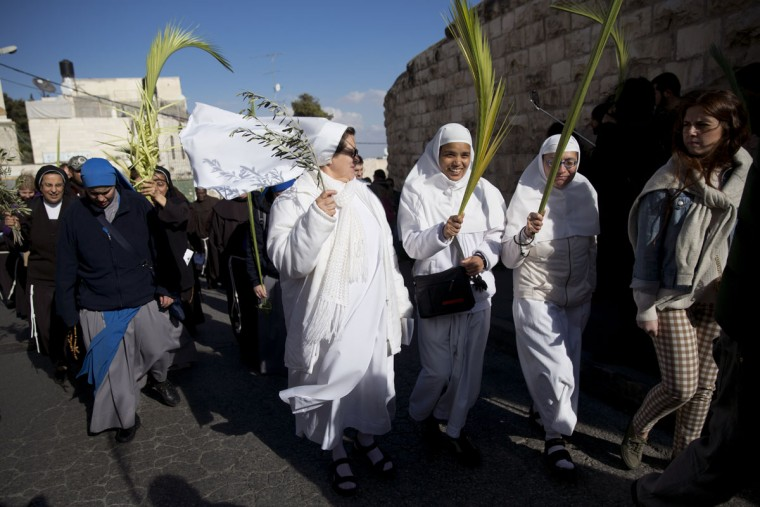 Christian nuns hold palm fronds during Palm Sunday procession on the Mount of Olives overlooking Jerusalem's Old City, Sunday, March 20, 2016. For Christians Palm Sunday marks Jesus Christ's entrance into Jerusalem when his followers laid palm branches in his path, prior to his crucifixion. (AP Photo/Oded Balilty)