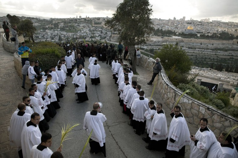 Christian priests, some holding palm fronds participate in the traditional Palm Sunday procession on the Mount of Olives overlooking Jerusalem's Old City, Sunday, March 20, 2016. For Christians Palm Sunday marks Jesus Christ's entrance into Jerusalem when his followers laid palm branches in his path, prior to his crucifixion. (AP Photo/Oded Balilty)